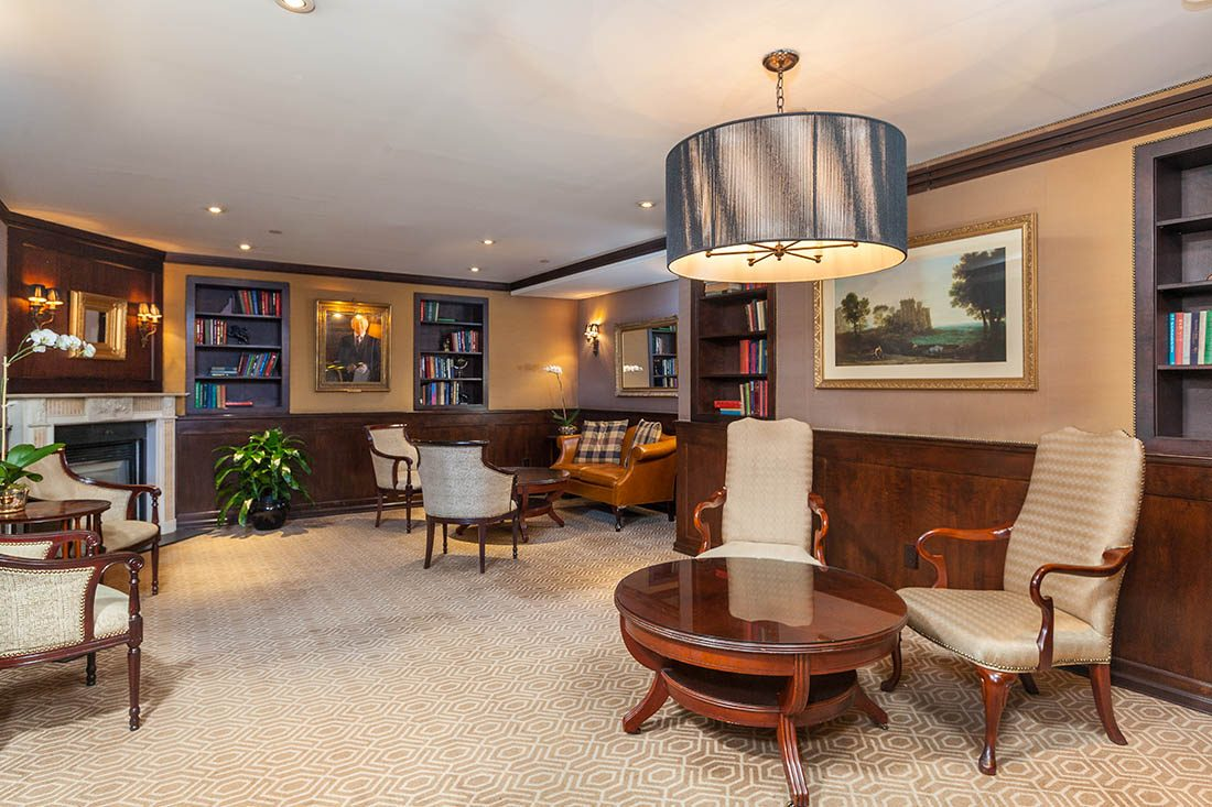 Seating area with two mini wall bookcases, cream armchairs and a framed picture of Irish President Michael Higgins
