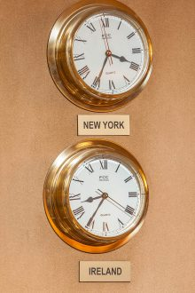 Twin gold clocks on wall, one showing New York time and the other showing the time in Dublin.
