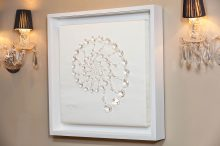 White framed arrangement of Jewels in the shape of a sea shell.