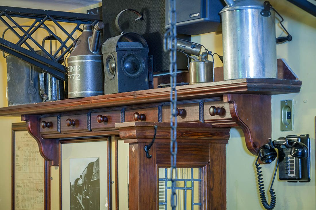 Old telephone and metal mementos on wooden shelf