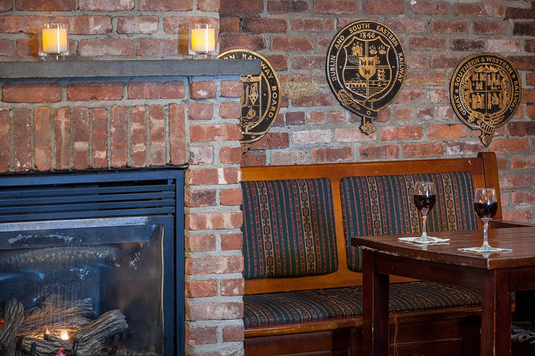 Seating booth at with a glass of alcohol on the table, fireplace to the left and Dublin railway wall decor on a brick wall.
