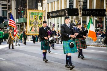 Male kilted marchers playing bagpipes in the streets of New York in the St Patrick's day Parade