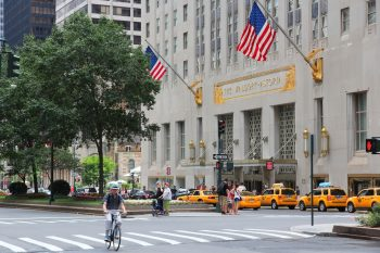 Exterior of the Waldorf-Astoria hotel in New York with American flags and people walking in the streets