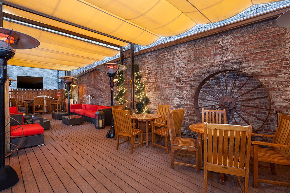 Outdoor seating under a canopy with pine tables and chairs and red cushioned outdoor couch and standing heaters.