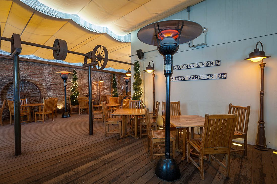 The Wheeltapper Pub and Patio with pine furnture and stadning outdoor heaters under a cream canopy.