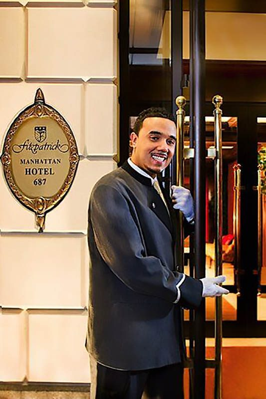 Smiling bellboy in front of Fitzpatrick Manhattan hotel signage.