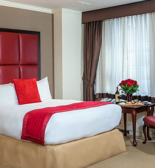 Fitzpatrick Deluxe Room with a bed, red accent pillows, leather headboard and breakfast with wine and flowers on the table.
