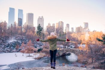 Female dressed in purple uggs, beanie and winter jacket standing on snow covered rock in Central Park