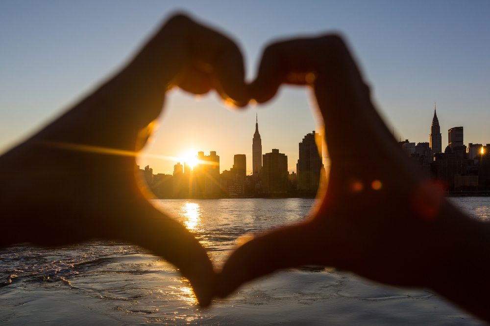 Hands in the shape of a heart around sun setting over New York city skyline