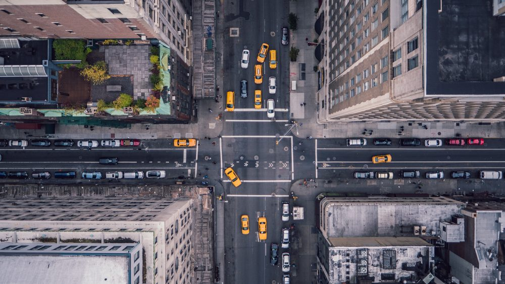 top-down view on cars an yellow taxi cabs in New York intersection amongst buildings