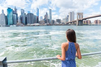 Woman admiring New York skyline from the back of a ferry