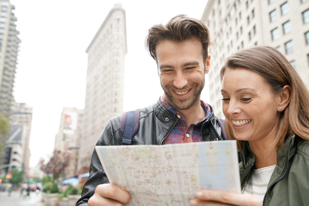 Smiling couple reading New York map