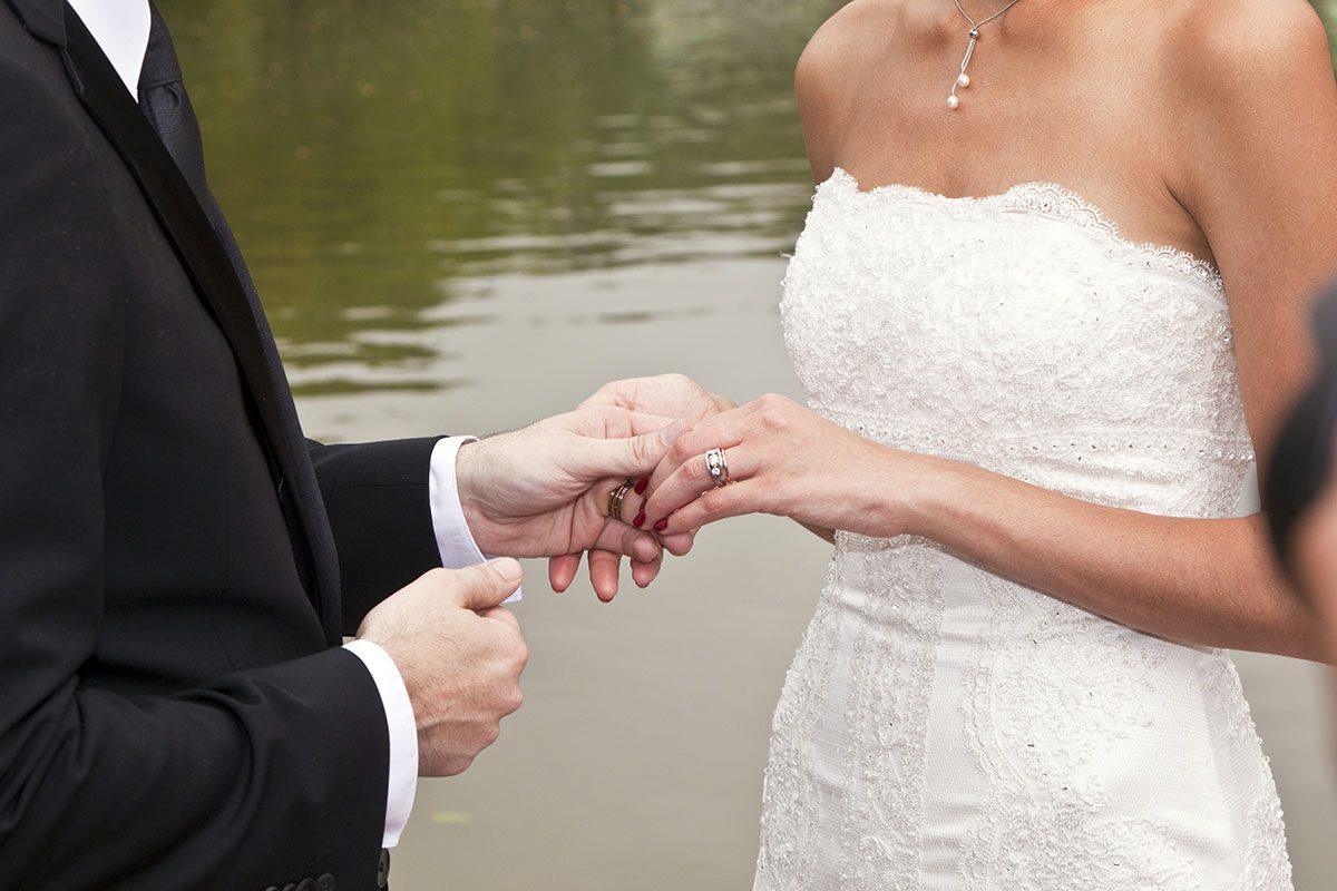 Married couple showing rings with bride in white wedding dress nad groom in suit in front of water feature