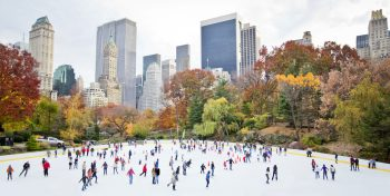 Ice skaters at Rockefeller centre against New York high-rise buildings in the background