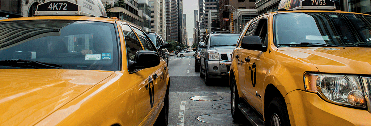 Signature New York yellow cabs on the right and the left on the streets of busy New York.